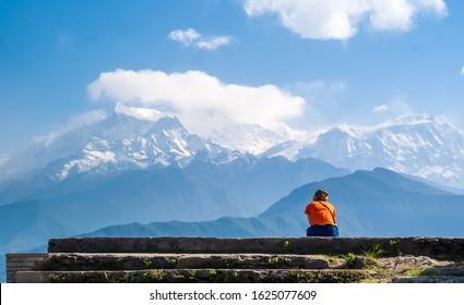 Young woman enjoying a Machapuchare (Fishtail) mountain and Annapurna range view, Himalaya. Sarangkot, Pokhara, Nepal.