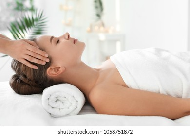 Young woman enjoying massage in spa salon