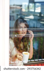 Young woman enjoying morning with cup of coffee, shot through balcony window