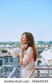 Young woman enjoying morning with cup of coffee on balcony