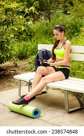 08437f35e91 Young woman enjoying the music sitting on the bench in sport wear. Rest and  relax