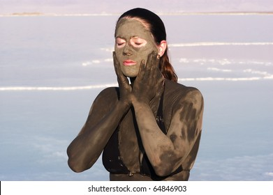 A young woman enjoying the natural mineral mud sourced from the dead sea, Israel. The Dead Sea known for its healthy minerals and as the lowest point on earth.(1,300 feet below sea level)