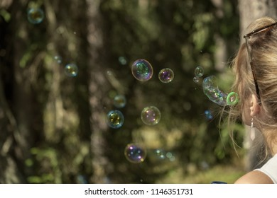 young woman enjoying nature trails in forest. vintage look. blowing soap bubbles