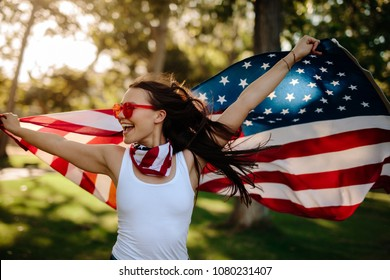 Young woman enjoying in park holding USA flag. American girl with national flag having fun at the park.
