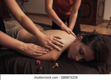 Junge Frau, die sich im Wellnessbereich mit vier Händen entspannen kann