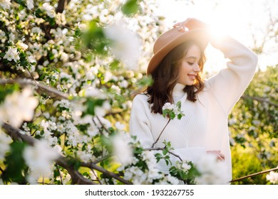 Young woman enjoying scent in blooming spring garden. The concept of youth, love, fashion and lifestyle.