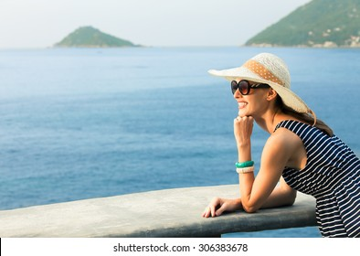 Young woman enjoying the sea side view from her hotel.