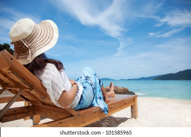 Young woman enjoying the sea view sitting on a beach's chair close to the sea