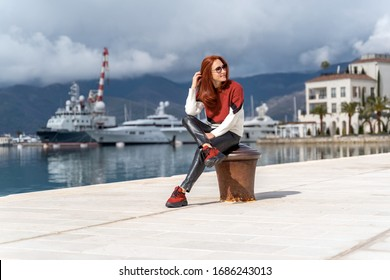 Young woman enjoying sea view in a marina port Montenegro.