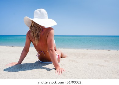 Young woman enjoying a sea view sitting on sand