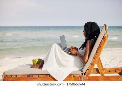 Junge Frau, die gerne in der Liegestube sitzt, auf dem Laptop arbeitet und auf die Meereswellen schaut