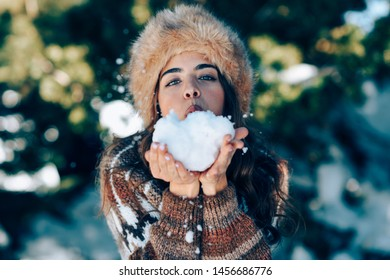 Young woman enjoying the snowy mountains in winter, in Sierra Nevada, Granada, Spain. Female wearing winter clothes playing with snow.