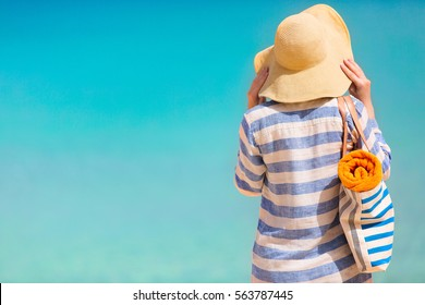 young woman enjoying summer vacation at perfect caribbean beach with turquoise water, copy space on left