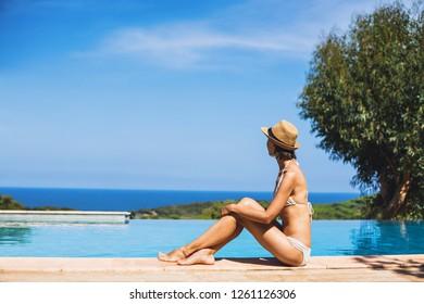 Young woman enjoying a sun near the infinity pool. Vacations, summer fun, enjoy life concept