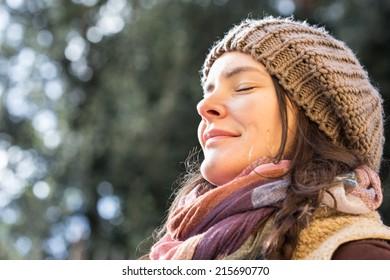 Young woman enjoying sunlight at the park.