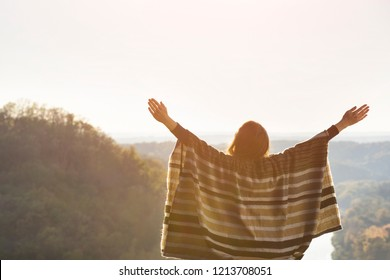 Young woman enjoying sunny day sitting on a hill. Raised hands. Back view