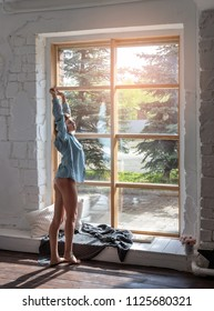 Young woman enjoying a Sunny morning standing by the large window of the room.
