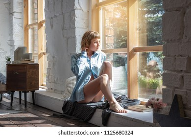 Young woman enjoying the Sunny morning while sitting at the large window of the room.