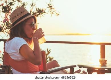 Young woman enjoying sunset at a beach bar