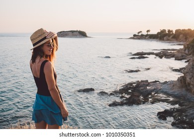 Young woman enjoying sunset on a cliff