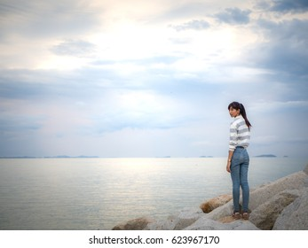 Young woman enjoying sunset in the seaside