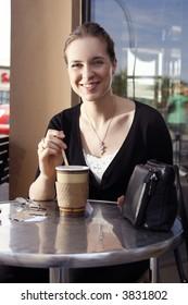 Young woman enjoying a tea at an outdoor cafe.