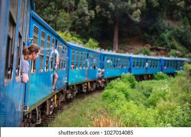 Young woman enjoying train ride from Ella  to Kandy among tea plantations in the highlands of Sri Lanka