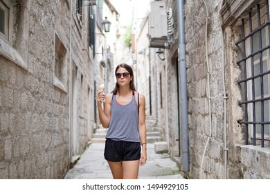 Young woman enjoying vegan ice cream, girl with sun glasses eating vegan ice-cream, sugar free, dairy free, outdoor, old city fortress in Kotor, wide shot