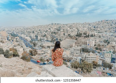 Young woman enjoying the view of the city from Amman Citadel or Jabal al-Qal'aa, a historic site from the Neolithic period in the heart of downtown Amman in Jordan in the Middle East
