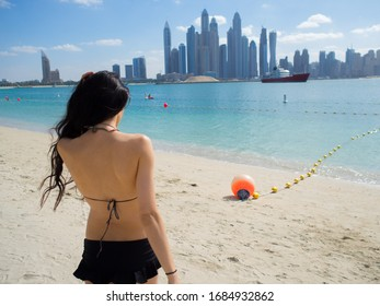 Young woman enjoying a view of Dubai sky scrappers from the beach, United Arab Emirates