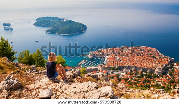 junge Frau mit Blick auf die Altstadt von Dubrovnik, auf dem Berg über der Stadt, Kroatien