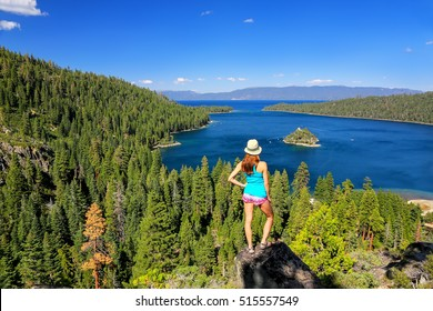 Young woman enjoying the view of Emerald Bay at Lake Tahoe, California, USA. Lake Tahoe is the largest alpine lake in North America
