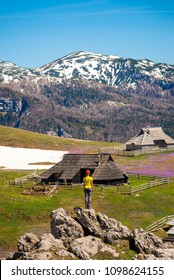Young woman is enjoying the view of Mountain huts or houses on idyllic hill Velika Planina / Big Pasture Plateau in spring with crocuses in Velika Planina, Slovenia.