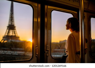 Young woman enjoying view on the Eiffel tower from the subway train during the sunrise in Paris