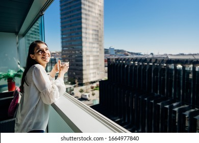 Young woman enjoying view on a sunny day with cup of coffee/tea on balcony in apartment in industrial/business area.Positive young woman living in skyscraper studio.Ready for the day.Business trip