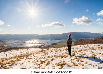 Young woman is enjoying the view over Lake Cerknica on a sunny winter day in Slovenia.