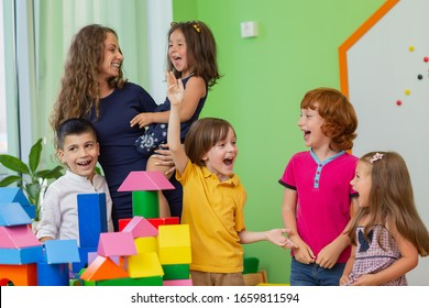 Young woman enjoying working as a teacher at elementary school, having fun with group of her little sutdents. Childhood, happiness concept