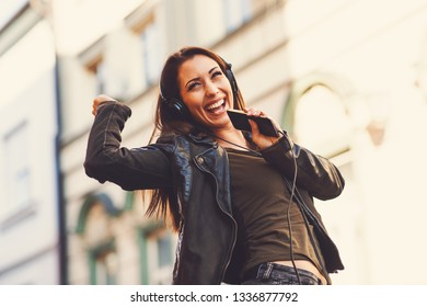 Young woman enjoys music on the street and dancing