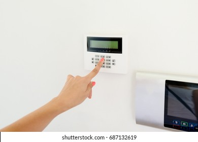 Young woman entering authorization code pin on home alarm keypad. Home security concept
