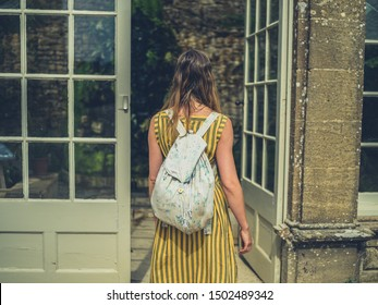 A young woman is entering an orangery