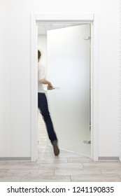 Young woman entering a room in modern office with minimalist white interior through frosted glass door. Woman is motion blurred