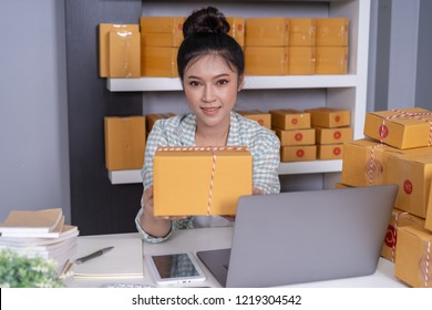 young woman entrepreneur with parcel boxes in her own job shopping online business at home