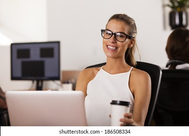 Young woman entrepreneur sitting at her computer and smiling in her startup office