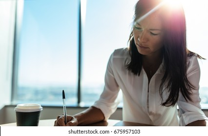 Young woman entrepreneur working at round table in office. Female business executive making business plans with a coffee cup on her table.
