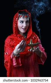 Young woman in ethic oriental clothes with genie lamp in hands on black background.