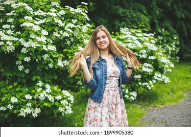 A young woman of European appearance with long blond hair, dressed in a short dress, stands against the background of white flowering bushes. Sunny spring day. Natural female beauty