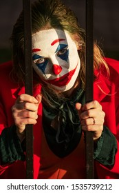 young woman with evil clown makeup and costume looking at camera through bars