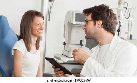 Young Woman In Exam Room With Ophthalmologist Using Digital Tablet
