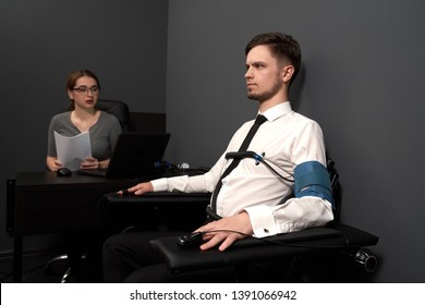 Young woman examinating man with lie detector. Suspect sitting at chair with attaching finger sensor and indicators and looking away. Woman holding paper and looking at computer polygraph.