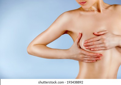 Young woman examining her breasts for signs of breast cancer isolated on a blue backgroundd